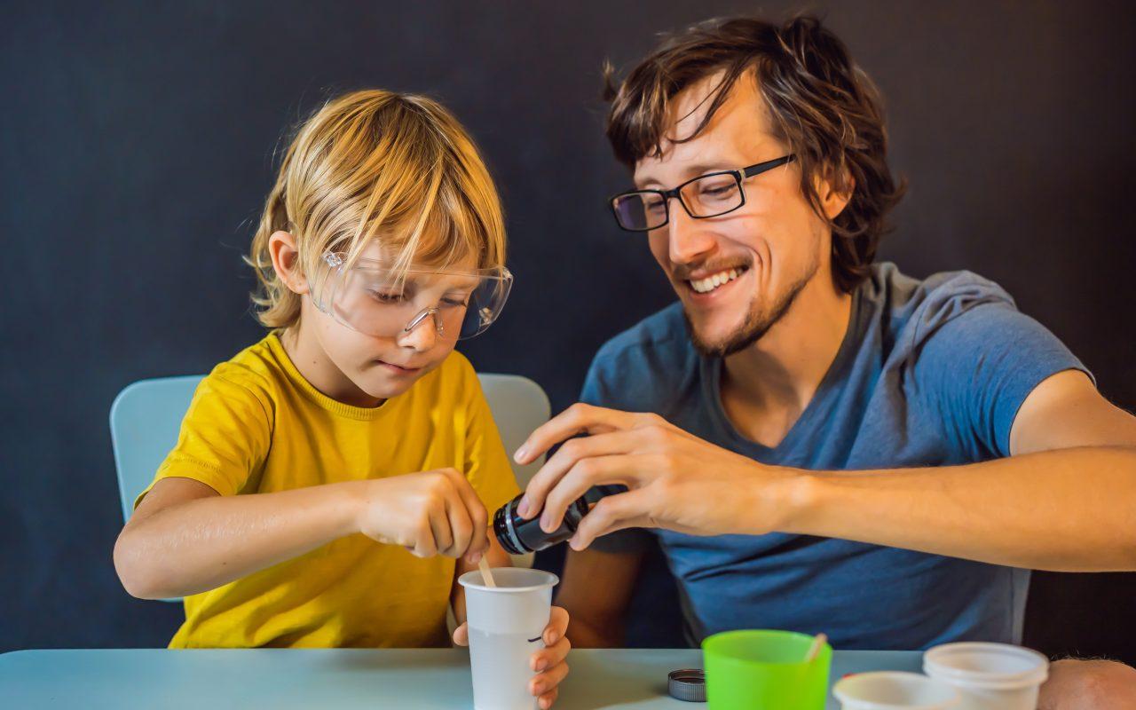 a boy and a teacher doing an experiment