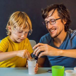 a boy and a teacher doing an experiment